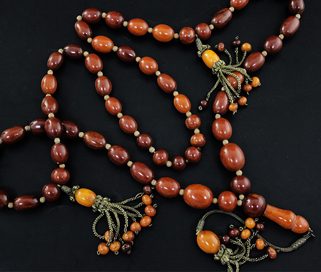 A Persian gilt metal and graduated amber bead tassel drop necklace